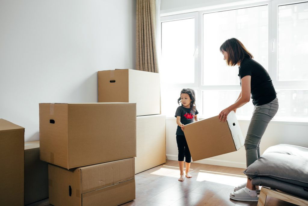 Young Woman And Daughter Moving Boxes